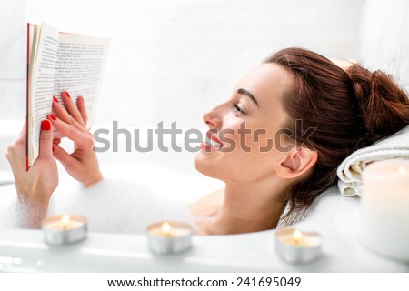 Young Woman Reading Book While Lying Stock Photo (Royalty Free ...