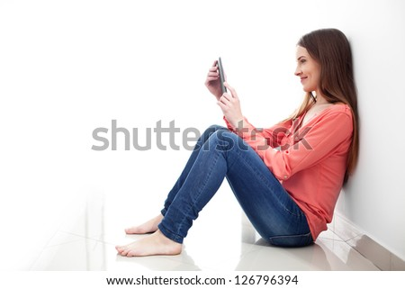 Young woman reading e-book while sitting on the floor