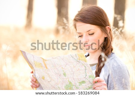 Young Woman Reading Map - This is a photo of a cute young woman sitting in tall grass in the woods reading a map. - stock photo