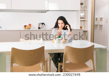 Young woman reading messages on mobile while having breakfast in a modern kitchen - stock photo