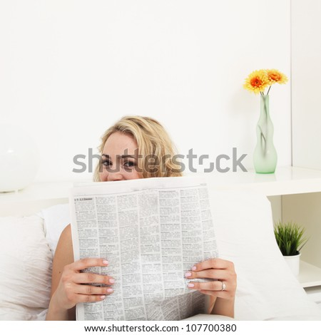 Young woman reading morning newspaper Young woman with an amused expression peers over the top of the morning newspaper which she is reading in bed - stock photo