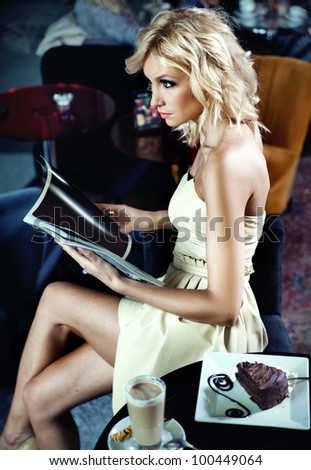 Young woman reading newspaper at a cafe - stock photo