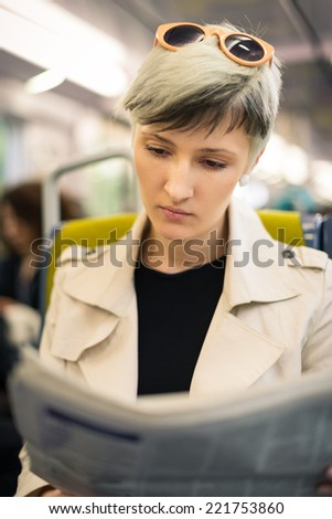 Young woman reading newspaper inside metro subway. Paris, France. - stock photo