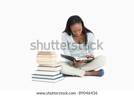 Young woman reading next to a stack of books against a white background