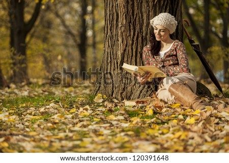 Young woman reading ni the autumn forest - stock photo