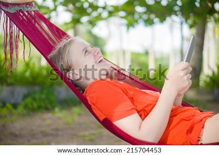 Young woman reading on electronic tablet reader relaxing in hammock under palm trees