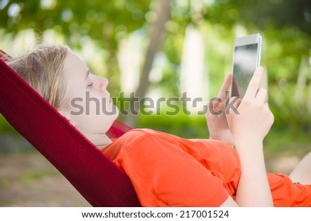 Young woman reading on electronic tablet reader relaxing in hammock under palm trees - stock photo