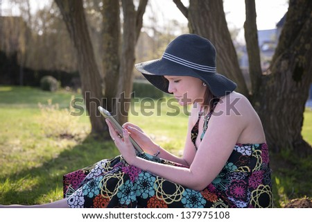 young woman reading outoors in the garden, under a tree