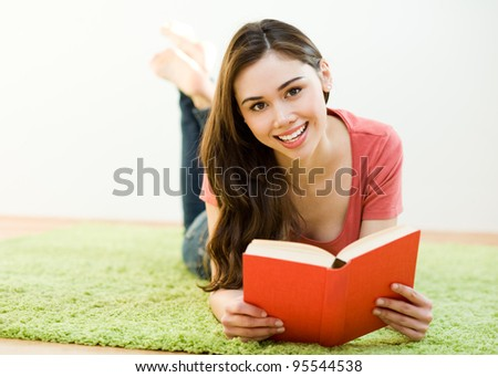 Young woman reading the book on green carpet at home