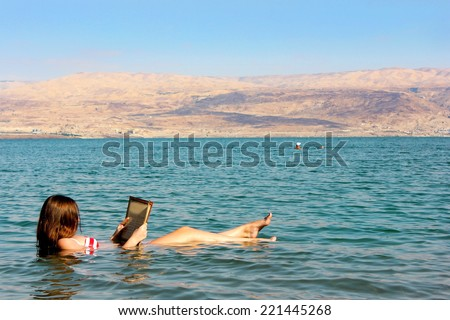 young woman reads a book floating in the waters of the Dead Sea in Israel - stock photo