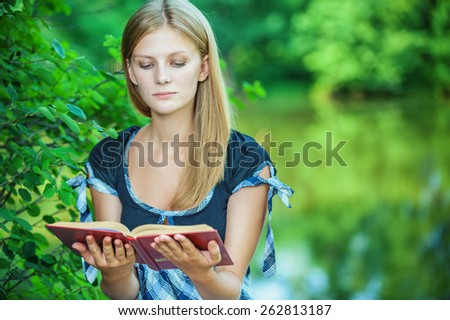 Young woman reads book and smiles, in summer city park.