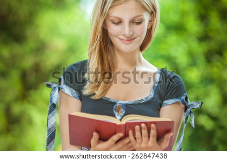 Young woman reads book and smiles, in summer city park. - stock photo