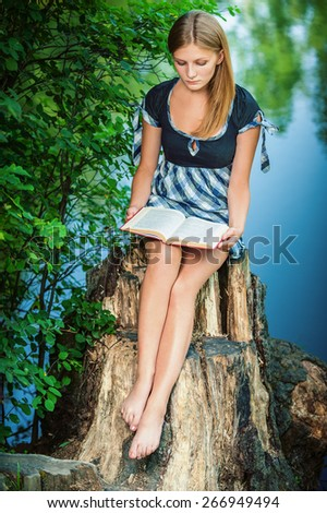 Young woman reads book on stub, in summer city park. - stock photo