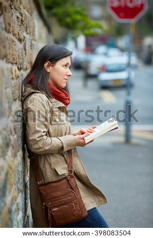 Young woman reads book on the street, urban shoot - stock photo