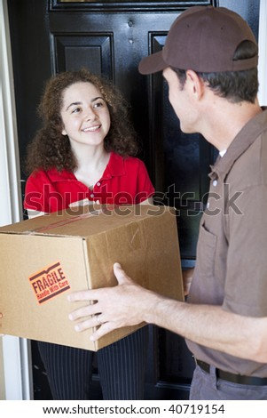 Young woman receives a home delivery from a courrier. - stock photo