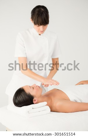 Young woman receiving alternative therapy at health spa - stock photo