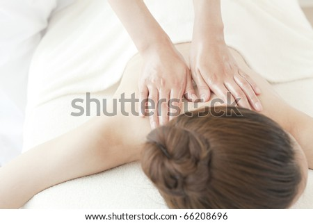 Young woman receiving back massage - stock photo