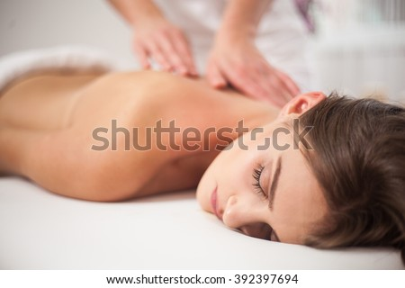 Young woman receiving back massage at spa