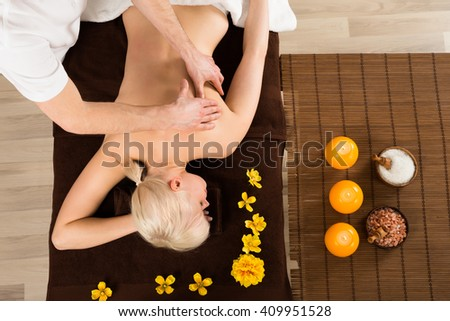 Young Woman Receiving Back Massage From A Massager In A Beauty Spa. High Angle View - stock photo