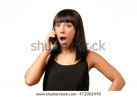 Young woman receiving bad news on her mobile listening to the call with a look of horror and consternation, upper body on white