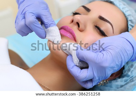 Young woman receiving beauty face therapy of cleaning pimple, acne. - stock photo