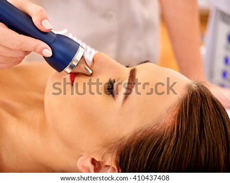 Young woman receiving electric facial massage. - stock photo