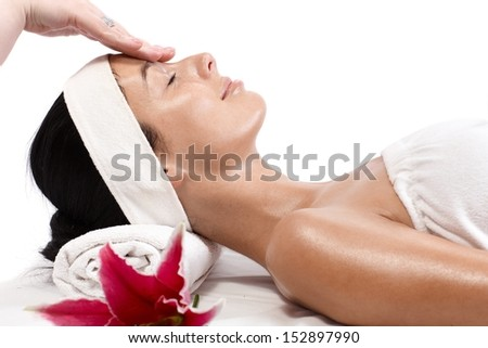 Young woman receiving facial massage, beauty treatment, side view. - stock photo