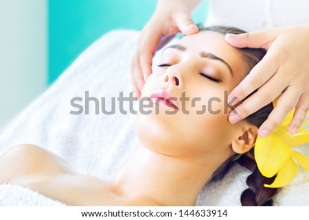 Young woman receiving head massage at spa - stock photo
