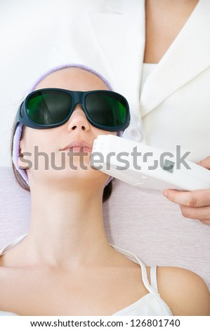 Young woman receiving laser epilation treatment - stock photo