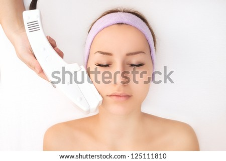 Young woman receiving laser treatment - stock photo