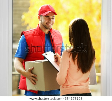 Young woman receiving parcel from delivery man - stock photo