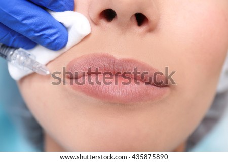 Young woman receiving plastic surgery injection on her face, closeup - stock photo