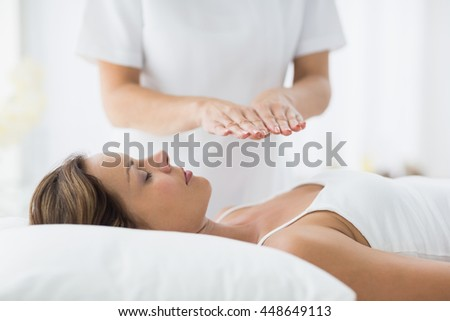 Young woman receiving reiki treatment at spa