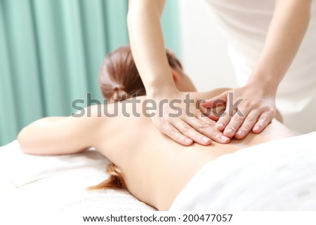 young woman receves back massage