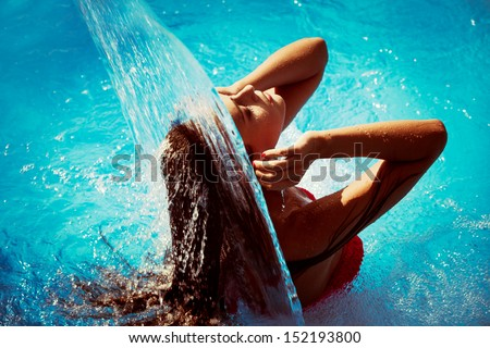 young woman refresh in pool under waterfall, retro colors - stock photo