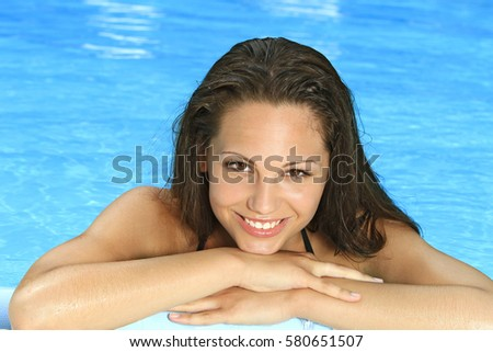 young woman refreshing in the swimming pool