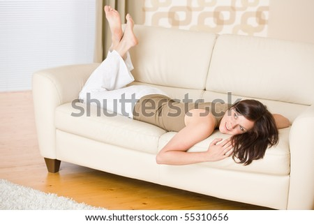 Young woman relax lying down on sofa in lounge