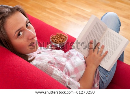 young woman relaxing and reading a book on a sofa - stock photo