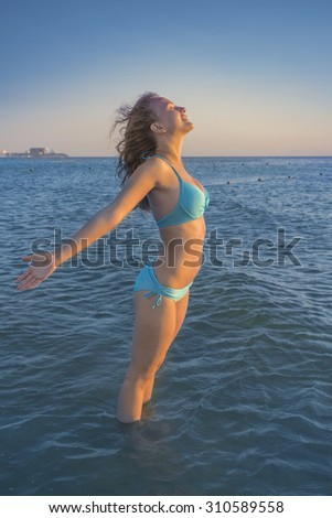 Young  woman relaxing and smiling on a beach near a blue sunny sea. Eternal summer concept. - stock photo
