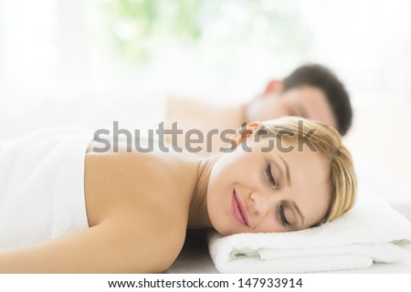 Young woman relaxing at health spa with man in background - stock photo