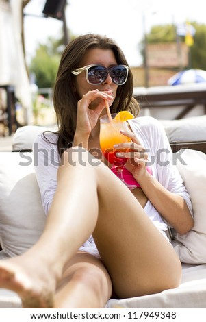 Young woman relaxing at summer lounge bar enjoying a fresh cocktail - stock photo