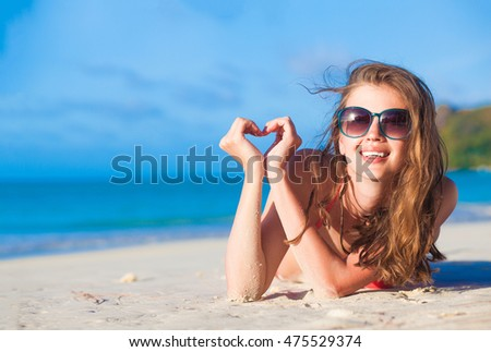 Young woman relaxing at the beach in the evening. Anse Volbert beach, Praslin island, Seychelles