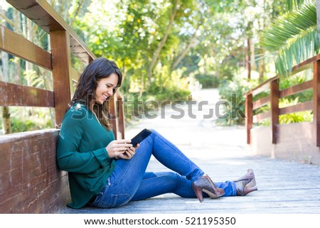 Young woman relaxing at the park with a tablet computer