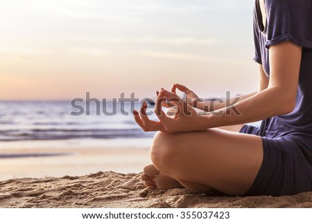Young woman relaxing by practicing yoga on the beach at sunset, close-up of hands, gyan mudra and lotus position