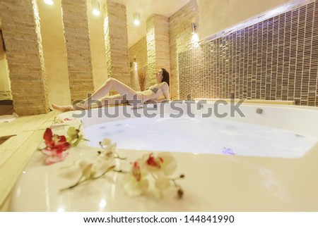 Young woman relaxing by the hot tub - stock photo