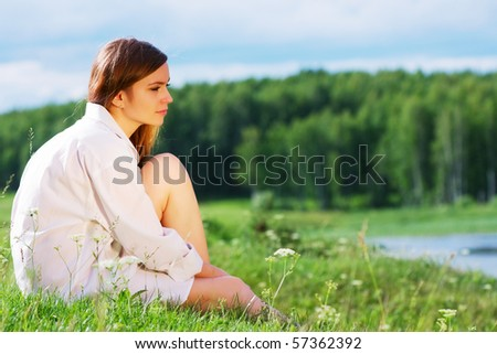 Young woman relaxing by the lake. - stock photo