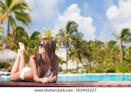 young woman relaxing by the tropical pool