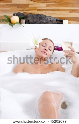 Young woman relaxing in a bath - stock photo