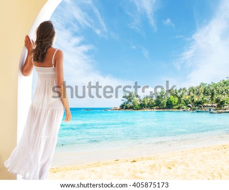 Young woman relaxing in a resort at summer. Girl in a white dress looking to a sea and sky.