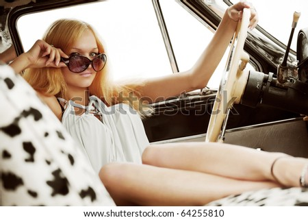 Young woman relaxing in a retro car.